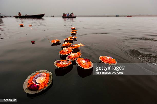 candles floating in the ganges river, varanasi, india - varanasi stock pictures, royalty-free photos & images