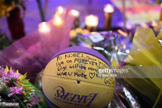 Candles flowers and a basketball are placed at a makeshift memorial as fans gather to mourn the death of NBA legend Kobe Bryant who was killed along...