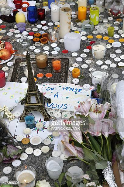 Candles flowers and a toy Eiffel Tower are pictured in front of the restaurant 'Le Carillon' at the crossroads of rue Bichat and rue Alibert in Paris...