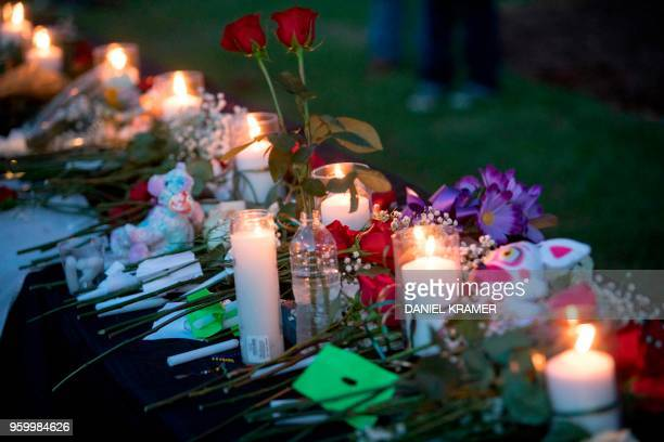 Candles flowers and stuffed animals line a table during a vigil in Santa Fe Texas for the victims of the mass shooting on May 18 2018 Ten people...