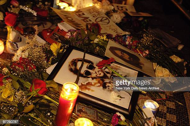 Candles flowers photographs and memorabilia cover the Imagine mosaic at Strawberry Fields in Central Park as people gather to commemorate the 25th...