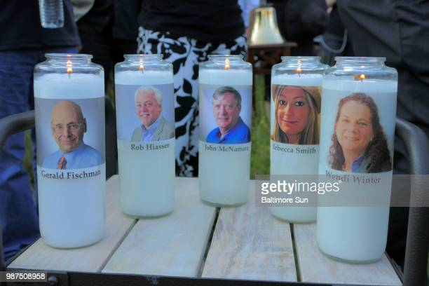 Candles honoring Gerald Fischman Rob Hiassen John McNamara Rebecca Smith and Wendi Winters flicker as the sun sets during a candlelight vigil on...