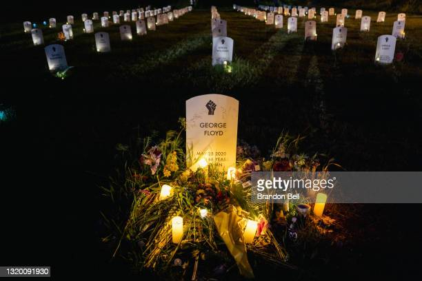 Candles illuminate a makeshift headstone for George Floyd at the Say Their Names Cemetery on May 25, 2021 in Minneapolis, Minnesota. People gathered...