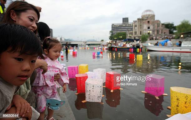 Candles in paper lanterns float in the Motoyasu River in front of the Atomic Bomb Dome at the Peace Memorial Park in memory of bomb victims during a...