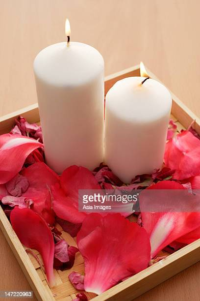 Candles in tray of petals.