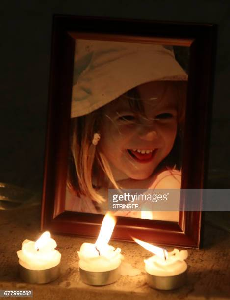 Candles light a photograph of Madeleine McCann inside the church of Praia da Luz near Lagos on May 3 during a mass ceremony marking the 10th...