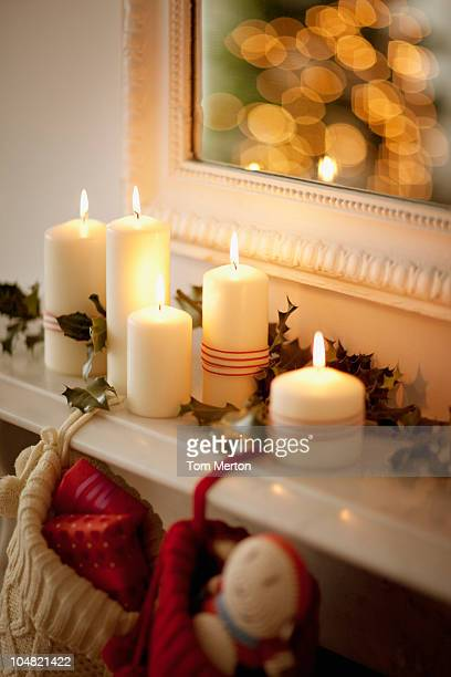 candles lit on mantelpiece with christmas stockings - vertical stock pictures, royalty-free photos & images