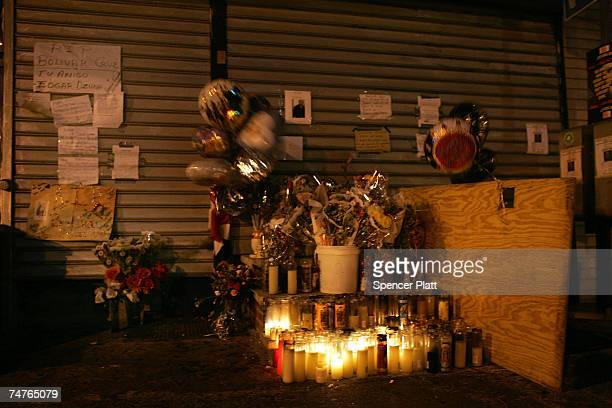 Candles notes and flowers form a vigil in front of the closed bodega where Bolivar Cruz was killed while working last week June 18 2007 in the Queens...