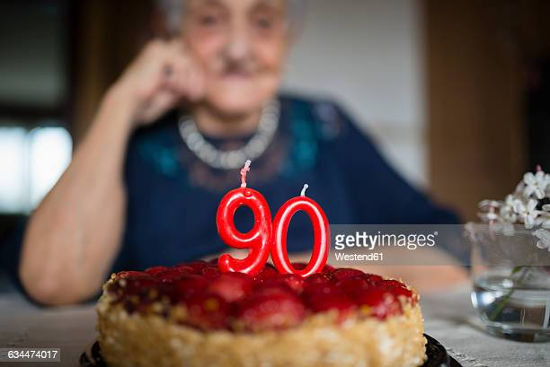 Candles on a birthday cake of a senior woman celebrating her ninetieth birthday