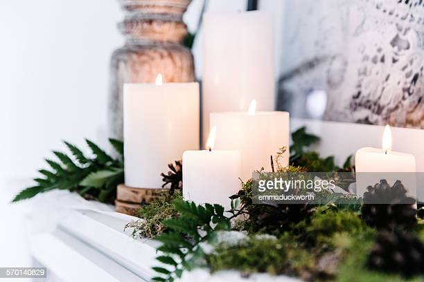 candles on a mantelpiece with foliage decoration - ローソク ストックフォトと画像