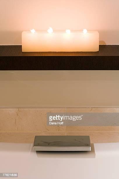 Candles on a shelf above a bathtub's modern stopper hardware