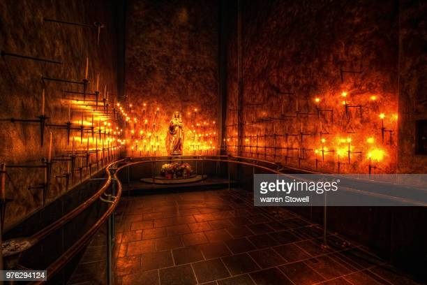 candles on walls around virgin mary statue - place of worship stock pictures, royalty-free photos & images