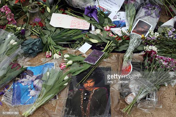 Candles purple flowers notes of condolences and images of musician and recording artist Prince are left at a makeshift memorial to the artist beneath...