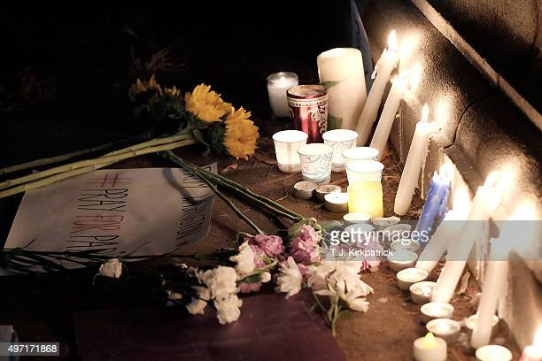 Candles signs and flowers lie at the base of a statue of Marquis de Lafayette during a vigil for victims of terrorist attacks in Paris at Lafayette...