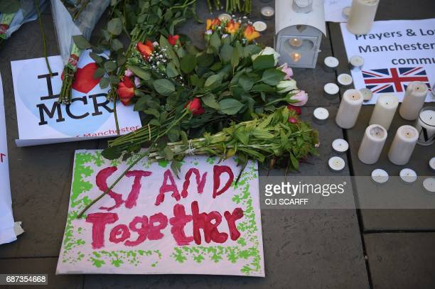 Candles sings and floral tributes left at a vigil in Albert Square are pictured in Manchester northwest England on May 23 in solidarity with those...