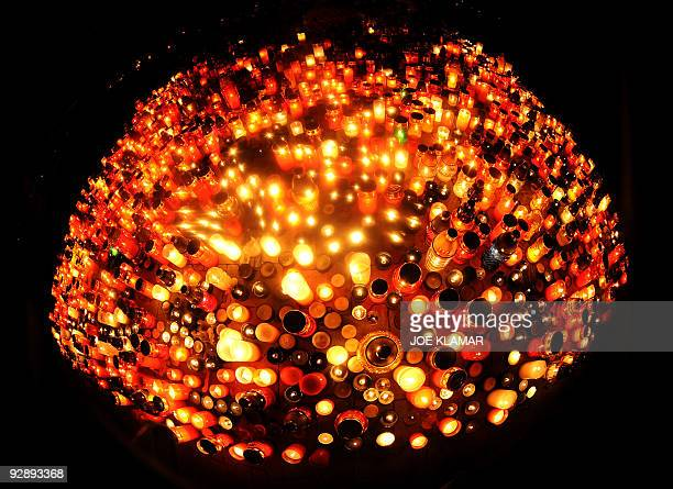 Candles sit in front of a cross during All Saints Day at the cemetary in central Slovak town of Liptovsky Mikulas on November 1 2009 AFP PHOTO/JOE...