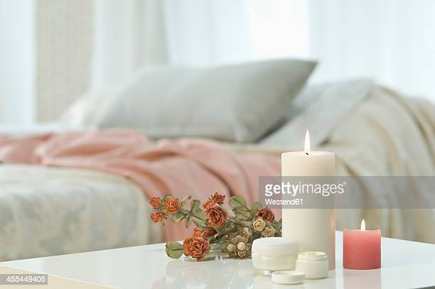 Candles, skin cream and bunch of roses on table with bed in background