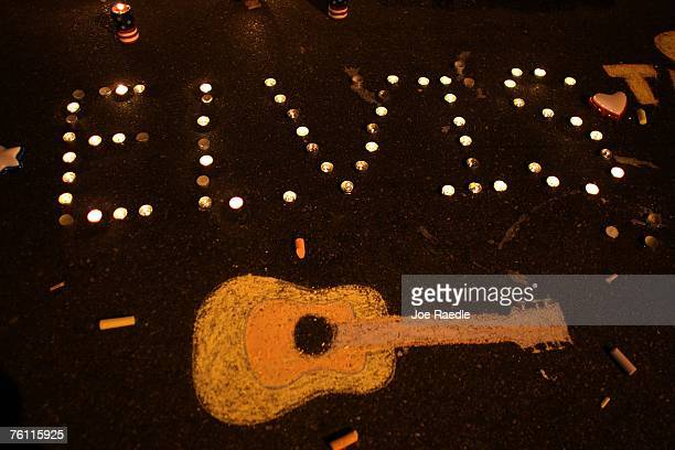 """Candles spell out """"Elvis"""" beside a chalk drawing of a guitar on the ground during a vigil held by fans in memory of the late singer outside the front..."""