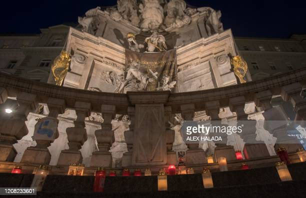 Candles stand at the plague column in Vienna's city center on March 25, 2020. - People placed candles as a sign of hope against the corona virus on...