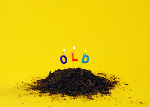 Candles stuck in dirt on yellow background. - gettyimageskorea