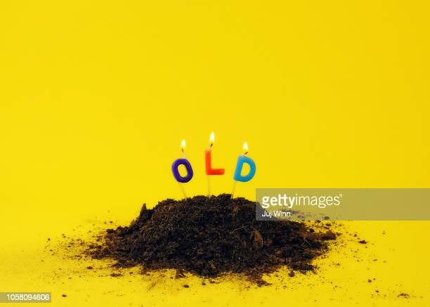 Candles stuck in dirt on yellow background.