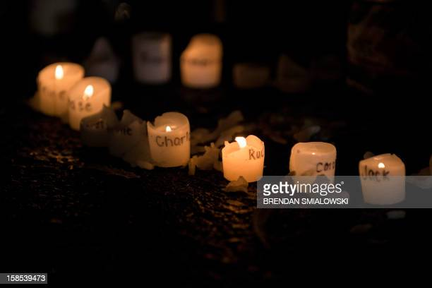 Candles with the names of victims of the Sandy Hook Elementary School shooting written on them are seen at a makeshift memorial near the entrance to...
