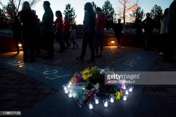 Candles wrap around a collection of flowers at the Columbine Memorial at Clement Park in Littleton Colorado during a community vigil for the 20th...