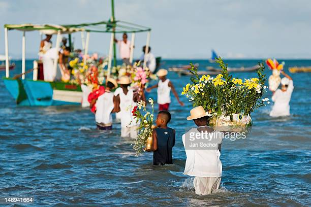 Candomblé devotees carry flower baskets onto a boat during the ritual ceremony in honor to Yemanjá the goddess of the sea on 3 February 2012 in...