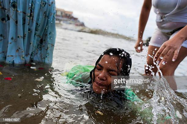 Candomblé follower becomes possessed in the water during the ritual celebration of Yemanjá the goddess of the sea on 2 February 2012 in Salvador...