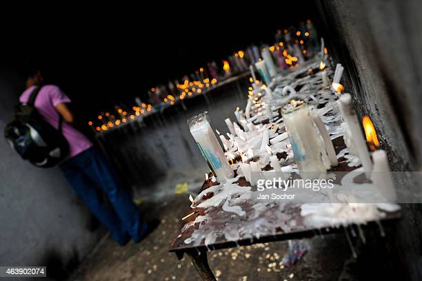 Candomblé follower offers a votive candle to Omolú the Candomblé spirit syncretized with Saint Lazarus outside the St Lazarus church on January 30...