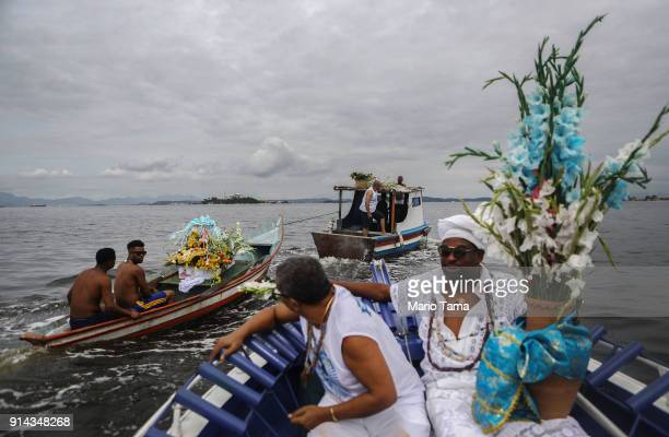Candomble followers ride boats towards the center of Guanabara Bay on their way to place flowers into the bay as offerings honoring Iemanja, Goddess...