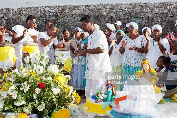 Candomble group in traditional white dress taking part in a public ceremony on the beach Offerings and flowers on a table in the foreground February...