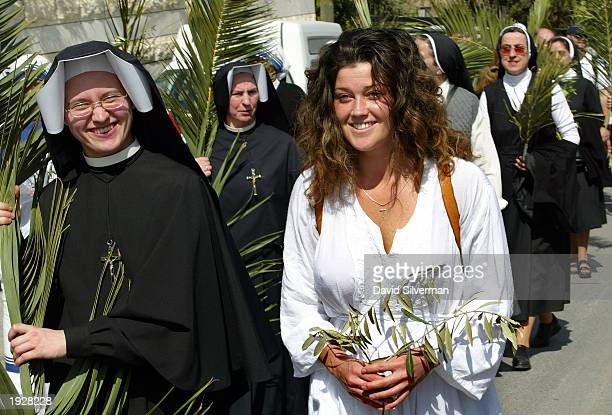 Candy a Christian pilgrim from the United tates accompanies Catholic nuns during the traditional Palm Sunday procession along the Mount of Olives as...