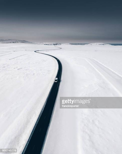 candy aerial view of snowed road in iceland - westfjords iceland stock photos and pictures