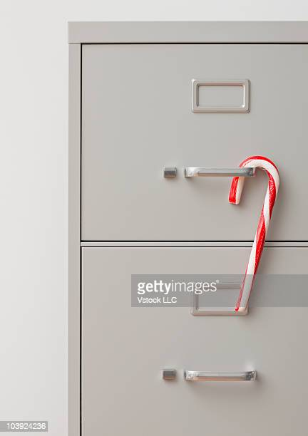 Candy cane hanging on filing cabinet handle