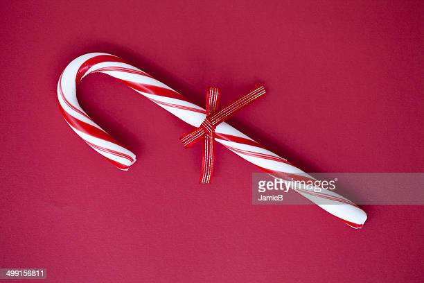 candy cane with a tied bow - candy cane stock pictures, royalty-free photos & images