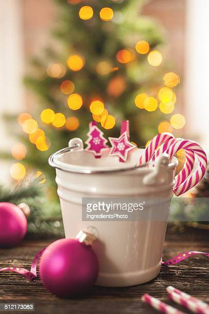 Candy canes in a small white pail on wooden table