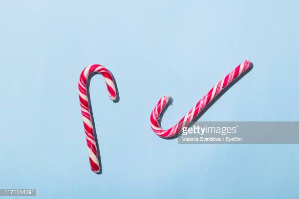 candy canes over blue background - candy cane stock pictures, royalty-free photos & images