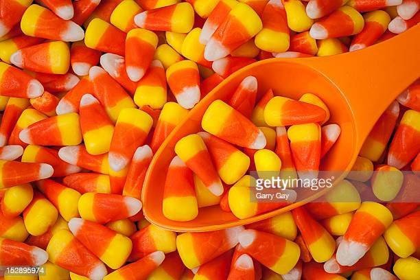 candy corn and orange scoop - candy corn stock photos and pictures