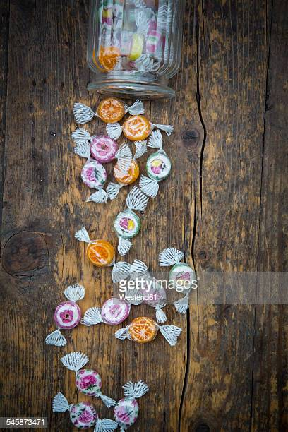 Candy jar and candies on dark wood