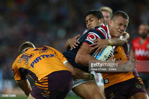 Cane Evans of the Roosters is tackled by Bronco's Dale Copley and Anthony Milford during the round 24 match between Sydney Roosters and Brisbane...
