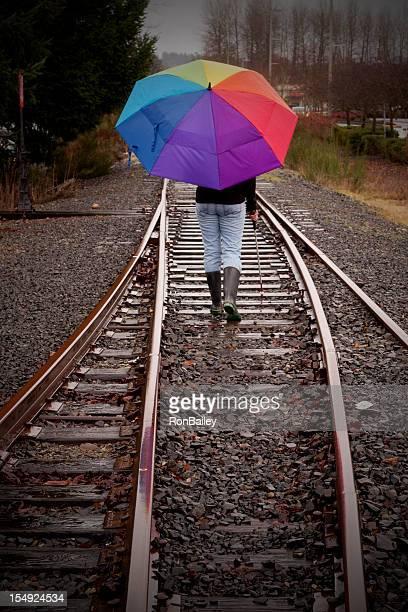 Cane User with Bright Umbrella On Railroad Tracks