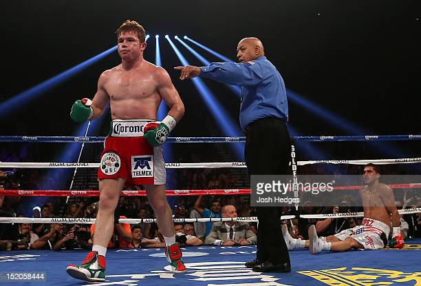 Canelo Alvarez is sent to a neutral corner by referee Joe Cortez after knocking down Josesito Lopez during their WBC super welterweight title fight...