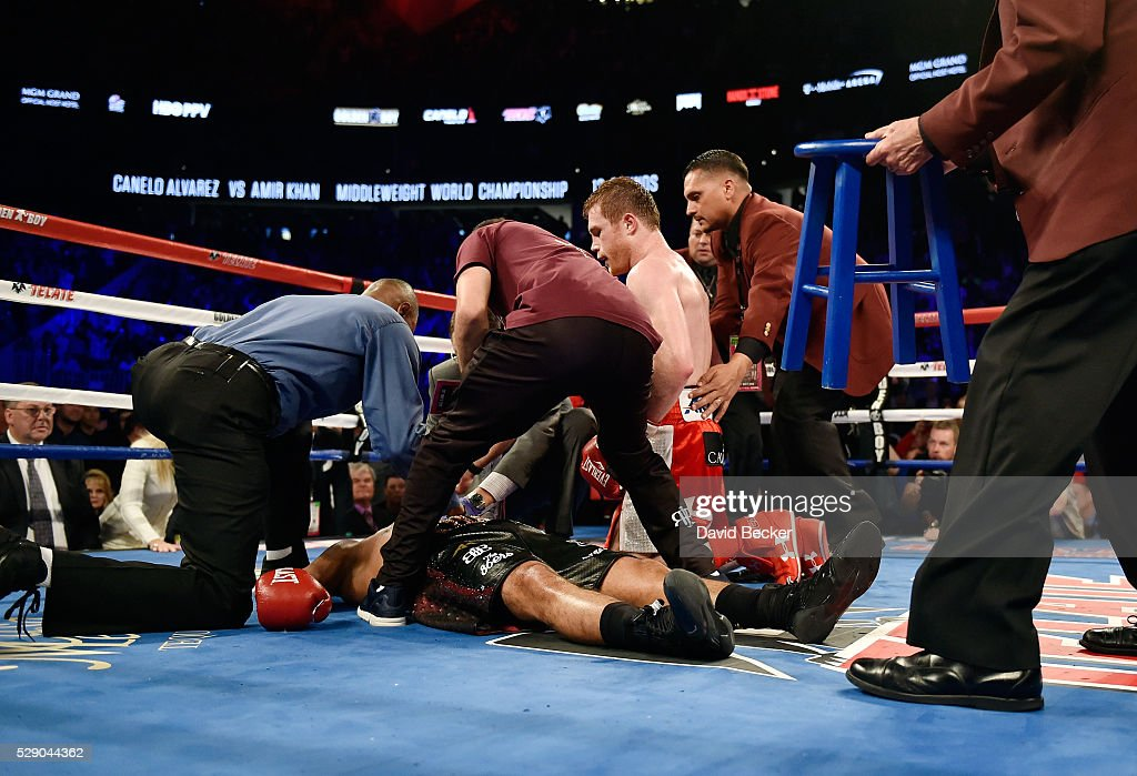 Canelo Alvarez (C) kneels over Amir Khan as officials tend to Khan after Alvarez delivered a knockout punch during the sixth round of their WBC middleweight title fight at T-Mobile Arena on May 7, 2016 in Las Vegas, Nevada.