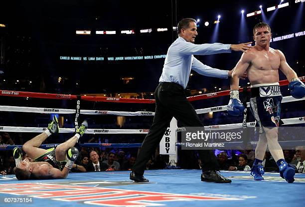 Canelo Alvarez right is lead to his corner after knocking down Liam Smith left during the WBO Junior Middleweight World fight at ATT Stadium on...