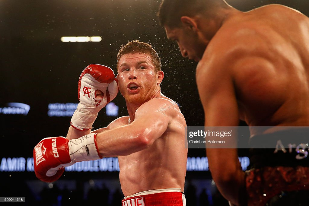 Canelo Alvarez (L) throws a left at Amir Khan during the WBC middleweight title fight at T-Mobile Arena on May 7, 2016 in Las Vegas, Nevada.