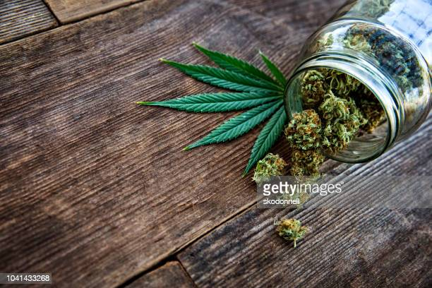 cannabis bud pouring out of a glass jar on wood background - legalization stock pictures, royalty-free photos & images