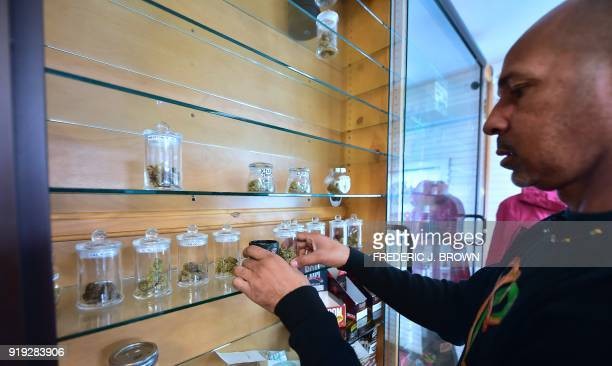 Cannabis entrepreneur Virgil Grant arranges containers of various strains of medical marijuana on a display case at a dispensary he runs in Los...