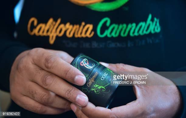 Cannabis entrepreneur Virgil Grant holds a 35 gram container for the medical marijuana strain 'California Cannabis OG' at a dispensary he runs in Los...