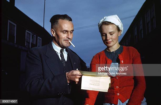 A cannery foreman gives papers to a cannery worker in Lubec Maine